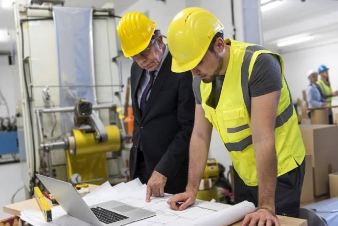 Un directivo y un ingenierorevisan unos documentos